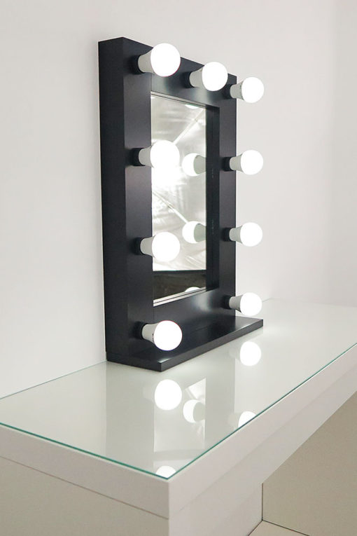 Schwarzer Schminkspiegel mit Glühbirnen mit 9 Lampen, auf einem Tisch.