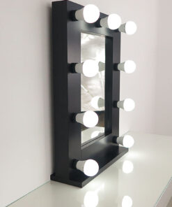 Schwarzer Theaterspiegel mit Glühbirnenmit 9 Lampen, auf einem Tisch.