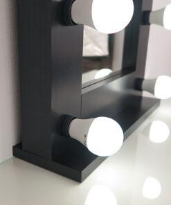 Schwarzer Theaterspiegel mit 9 Lampen, auf einem Tisch.