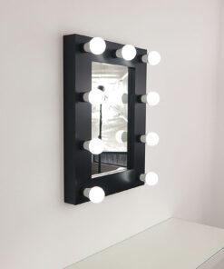 Svart teater speil med 9 lamper, mot en vegg.